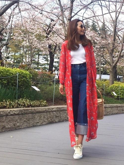 花柄プリントのガウンに、白いコンバースのスニーカーを合わせた着こなしです。大きく足首を見せたスタイルが、軽やかなイメージを演出しています。