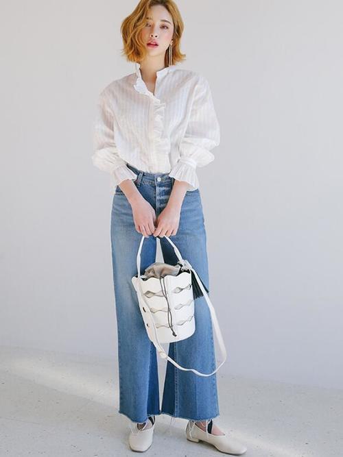 たっぷりボリュームの袖にラッフルの袖がかわいい白いブラウスにデニムをあわせてスッキリとスタイリング♪カジュアルな印象のデニムも、靴や小物を白で統一することによりシックな印象になりますね。