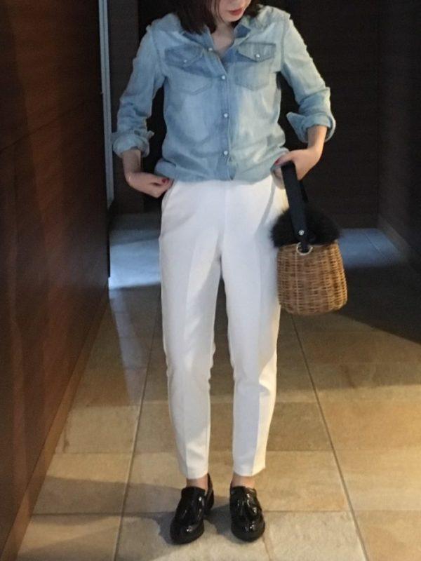 デニムシャツと白のテーパードパンツとのコーディネート。シンプルな色合いのスタイリングに、黒のローファーと流行の黒アクセントのカゴバックのアクセントが印象的です。