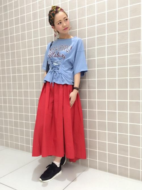 着るだけで楽しい気分になれそうなコルセットトップス。その青とは対照的な赤いスカートを合わせて、ポップなカジュアルを楽しんで。