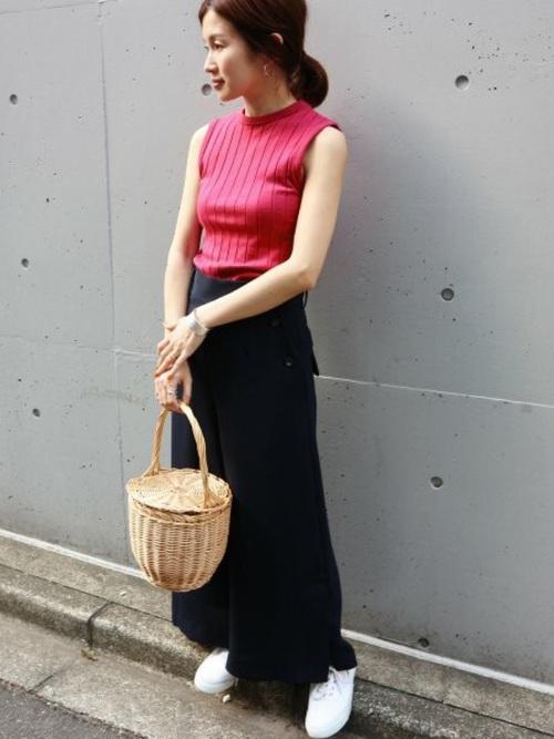 派手色ピンクのノースリーブのトップスに黒のワイドパンツを合わせた大人かっこいい着こなしです。大きめなかごバッグで可愛らしさもプラスしています。