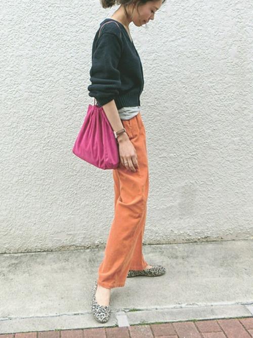 ネイビーのトップスとオレンジのパンツにヒョウ柄パンプスの組み合わせ♪カジュアルな着こなしに派手色ピンクの巾着バッグをアクセントに取り入れています☆