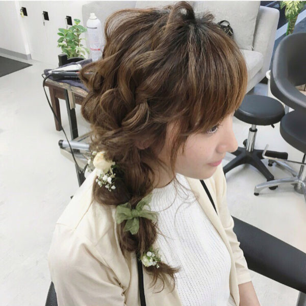 ロングヘアだと前に寄せ編みをして大人なスタイルを楽しめますね。グリーンのリボンとホワイト系のお花がナチュラルです。