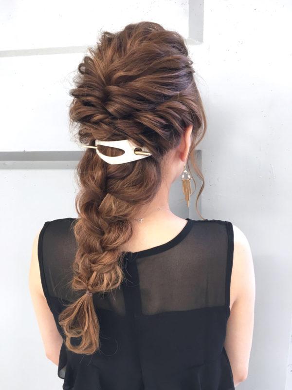 ハーフアップした髪を三つ編みにまとめたヘアアレンジ。イヤリングとテイストを合わせてゴージャスなヘアスタイルになっています。