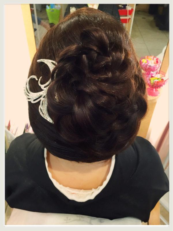 編み込みが素敵なヘアスタイルになっています。かんざしもヘアスタイルをより華やかに見せるように、ゴージャスなものを。曲線がフェミニンです。