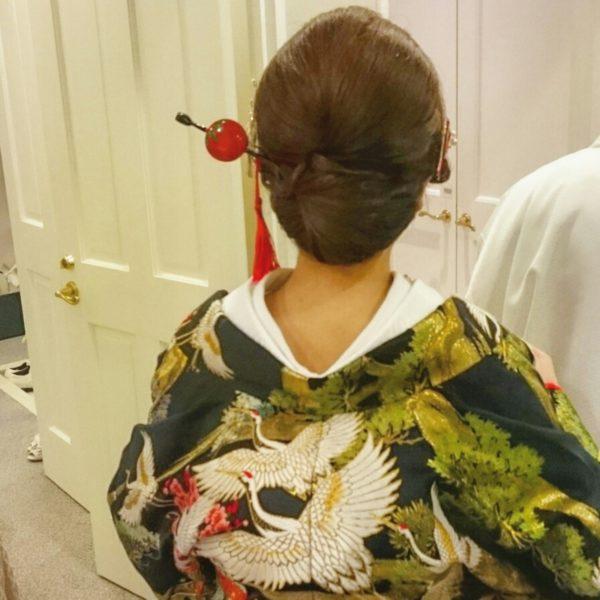 赤い玉が印象的なかんざし。かんざしに存在感があるので、ヘアスタイルはシンプルなまとめ髪で。