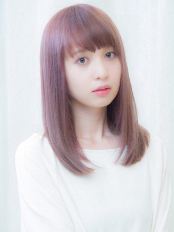 フリンジバングヘアはピンクカラーで柔らかい色彩を加えて、大人かわいいヘアに。目元の印象が残りやすい。