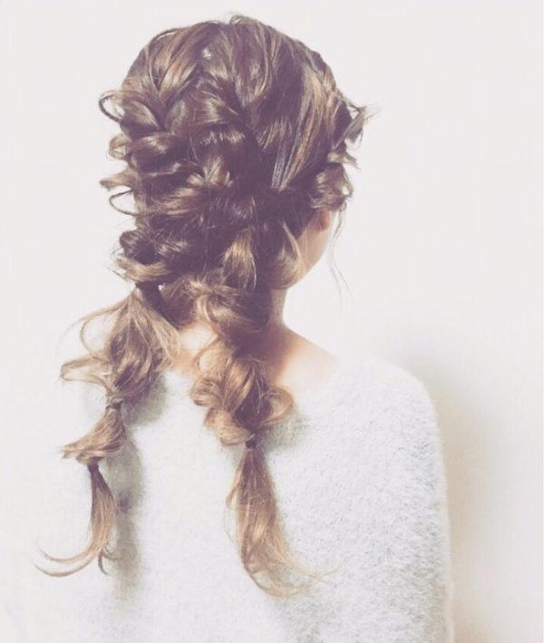 ゆるふわのロングヘアを、ツインテールに編み込んだヘアスタイル。ところどころで大胆に髪を引き出してこなれ感をプラス。
