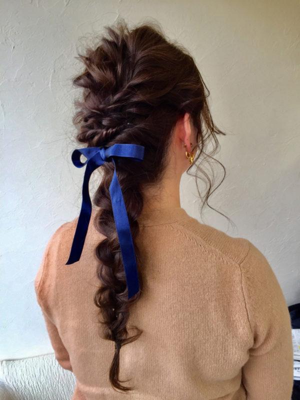 編み込みしたスタイルにブルーのリボンをつけて、クラシカルに。シンプルなファッションのアクセントに。