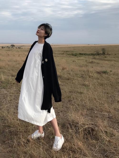 風をはらむようなゆったりシルエットのドレスにオーバーサイズのアウターを羽織って独特のシルエットをつくっていますね。白スニーカーがイノセントな印象をもたらします。
