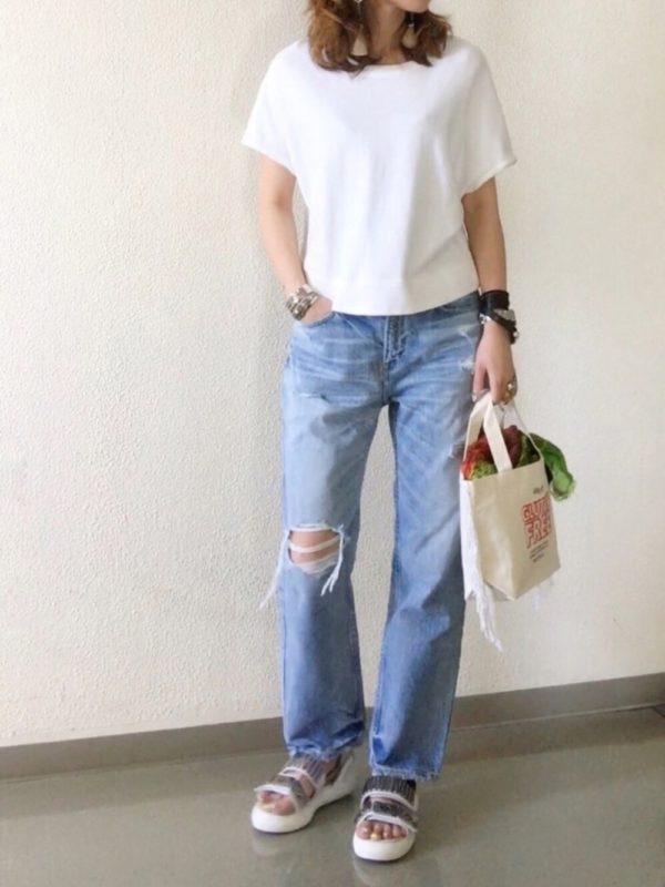白Tシャツとデニムパンツの鉄板コーデ。さりげなさがお洒落ですね。飾らない雰囲気がありつつも、ダメージ加工された部分がアクセントになっていて、計算されたカジュアル感がいいですね。手首にアクセサリーを身につけて、メリハリをつけて。