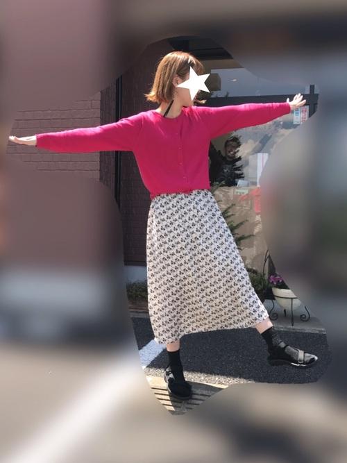 ビビットピンクのカーディガンと白ベースの花柄スカートを合わせたコーディネートには、黒靴下と黒サンダル!カラーコーデがぐっと引き締まります!