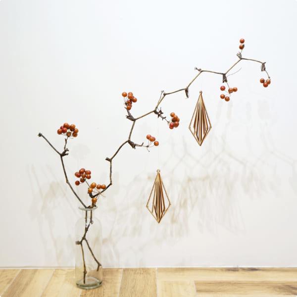 北欧の木製オーナメントを赤い実のある枝に飾って