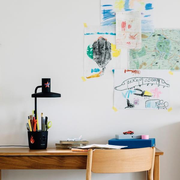 スタディデスクの上の壁に子供の絵や地図を貼って