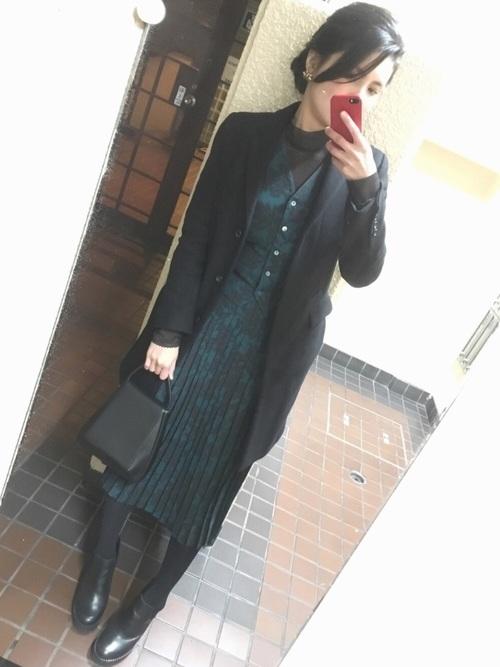 黒でまとめたオフィスカジュアルの柄物スカートスーツコーデ