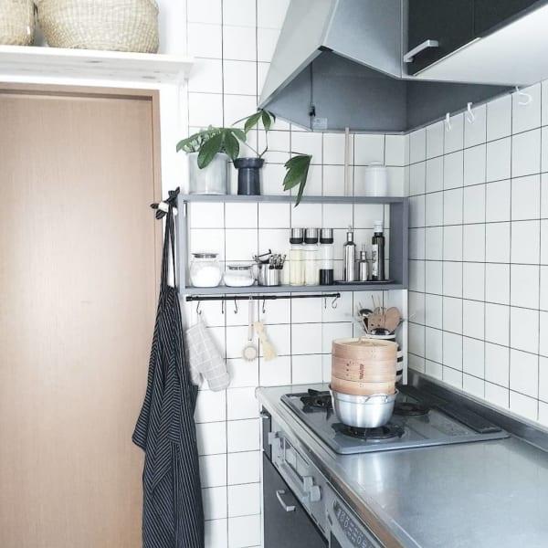 白いタイルの壁にグレーの家具が映えるキッチン
