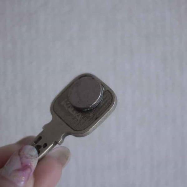 超強力マグネットでカギをドアに貼り付ける