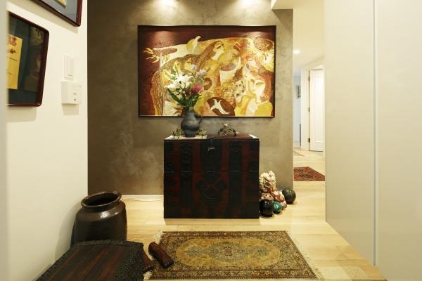 メタリック珪砂の塗装を施した壁が油絵を引き立てる。この壁にピンときて、物件の購入を決断。