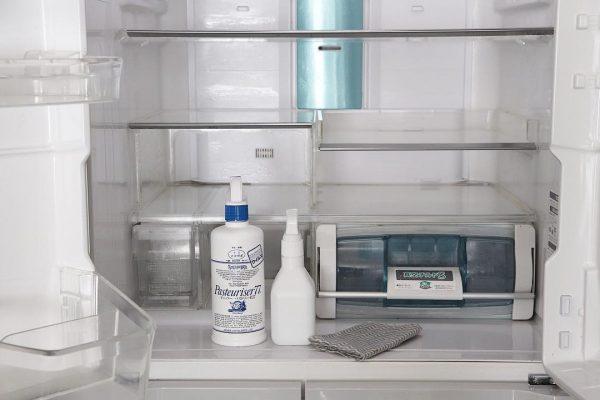 冷蔵庫の棚をアルコール除菌剤で拭き上げる