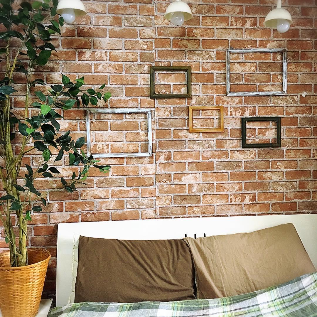 茶色の枕カバーがレンガ調の壁紙にマッチ