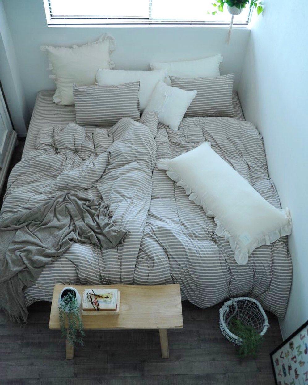 ベッドリネンやクッションがおしゃれな寝室