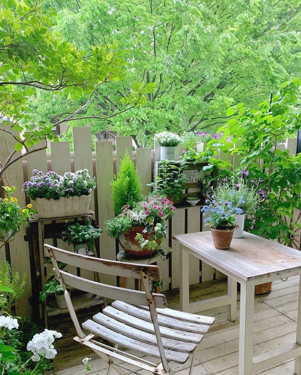 戸外の樹木と一体感のあるベランダのお庭