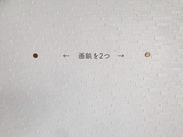 壁に画びょうを2つ刺す