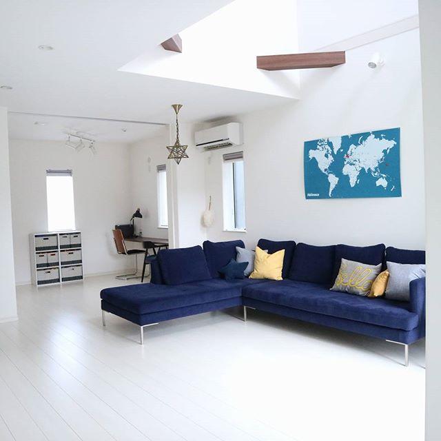 青いソファを白いリビングに置いた実例