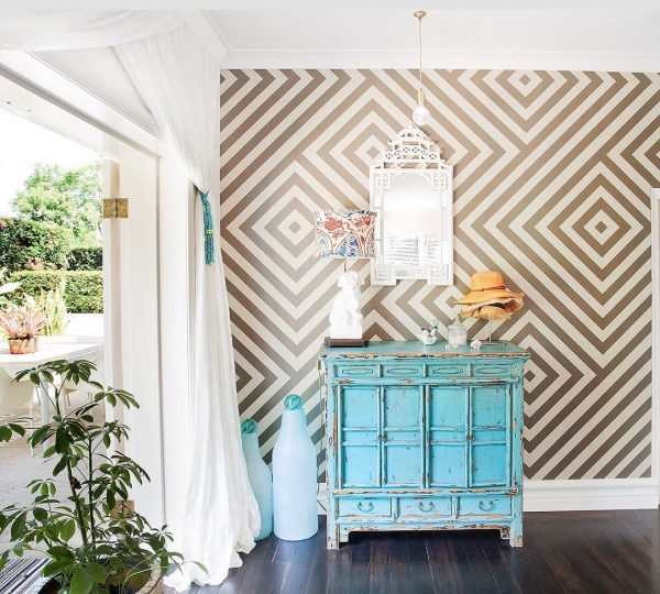 幾何学柄の壁紙とアンティーク家具が好バランス