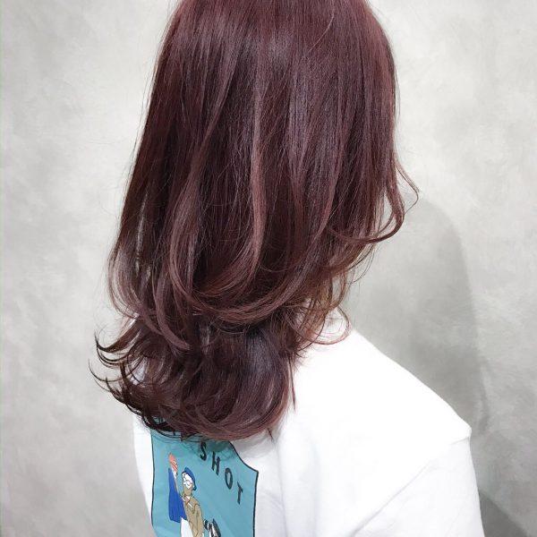 軽やかな印象の暗めピンクのミディアムヘア