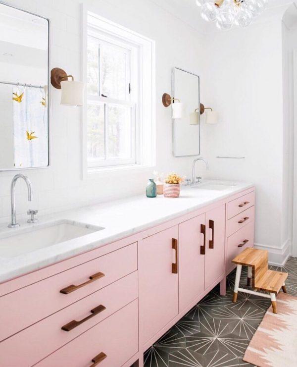 白いバスルームにあるピンクの洗面台