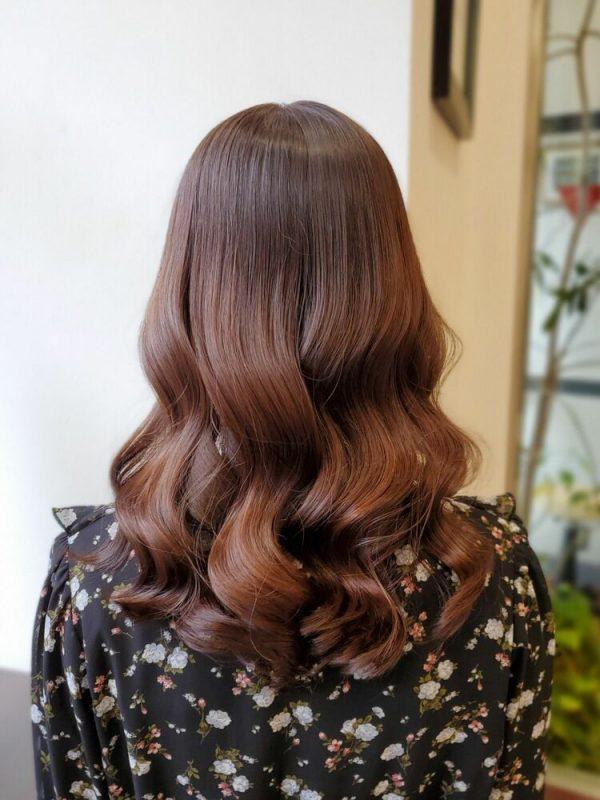 暖かいライトブラウンの髪色の巻き髪ヘア