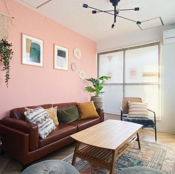 ピンクの壁紙とブラウンソファのインテリア