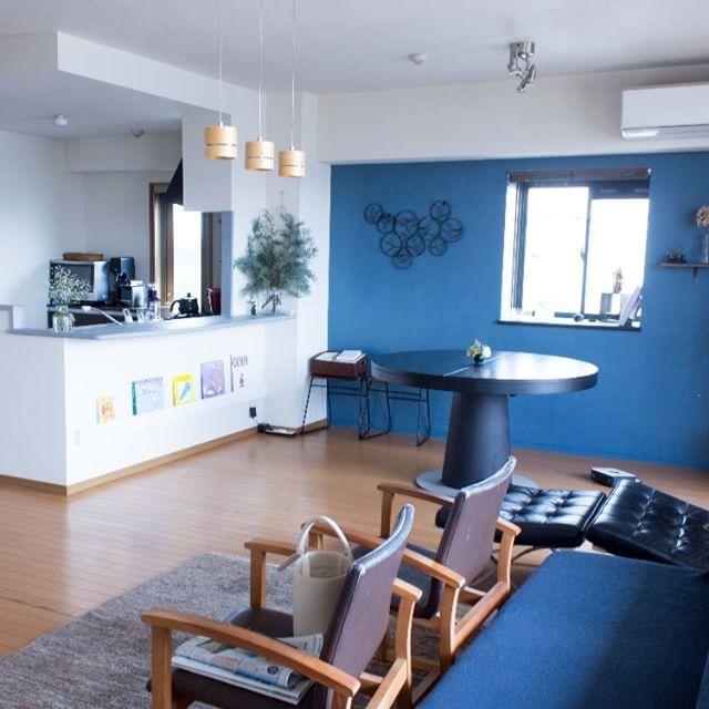 ブルーの壁と家具のリビングダイニング