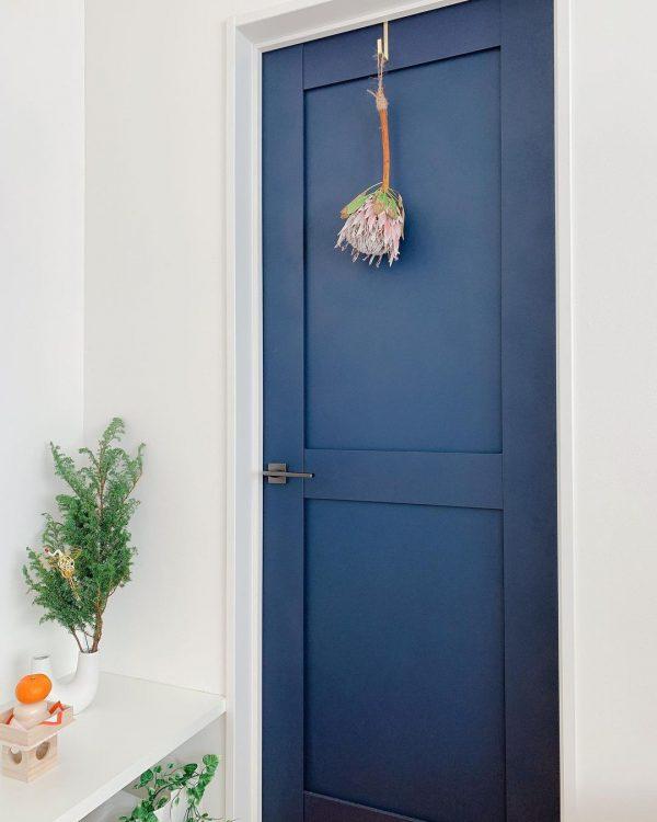 青い扉にゴールドのフックをかけるインテリア