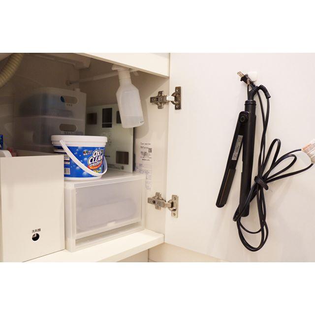 洗面台下のドア裏にヘアアイロンを収納