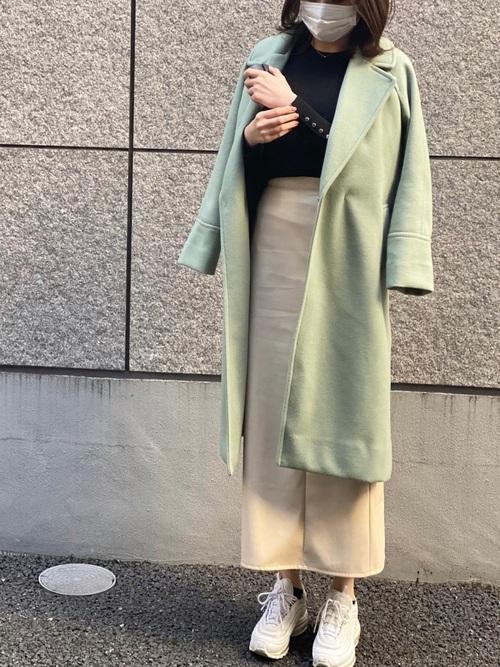 緑コート×ベージュスカートの女性向けコーデ