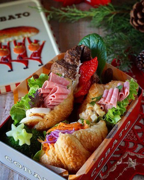 クロワッサン、サンドイッチ、お弁当、ゆで卵、ハム、レタス、人参、サラダ、イチゴ。