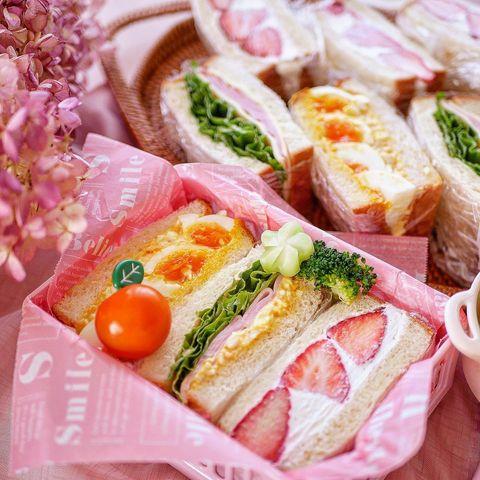 サンドイッチ、お弁当、卵、レタス、ハム、イチゴ、クリーム、ブロッコリー、ミニトマト。