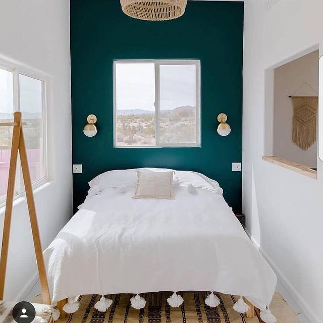 シックな緑色のアクセントクロスの寝室